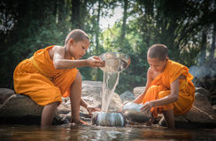 Buddhist novices are cleaning bowls at the creek. stock image