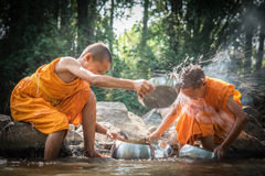 Buddhist novices are cleaning bowls and splashing water in the s Royalty Free Stock Photos