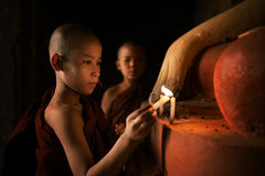 Buddhist novices praying with candlelight in monastery Stock Photography