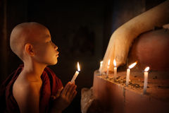 Buddhist novices praying with candlelight in temple. Portrait of young novice monk praying with candlelight inside a Buddhist temple, low light setting, Bagan Stock Photo
