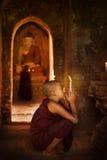 Buddhist novices praying in monastery royalty free stock photo