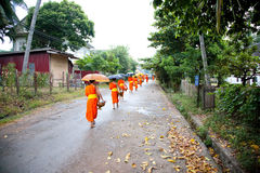 Buddhist novices walk to collect alms Stock Photo
