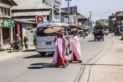 Buddhist nuns. Are crossing a street at Dawei, Myanmar. They are wearing parasols royalty free stock photos