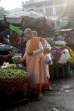 Buddhist nuns recieving alms at Zegyo Market stock photo