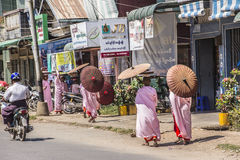 Buddhist nuns. Are walking along a street at Dawei, Myanmar. They are wearing parasols royalty free stock images
