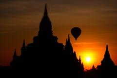 Buddhist Pagoda silhouette and balloon at sunrise. Bagan, Myanmar Stock Photography