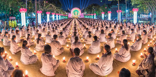 Buddhist panorama sitting hands in prayer in candlelit Stock Photos