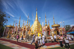 Buddhist people praying and walking around a golden pagoda. Stock Image