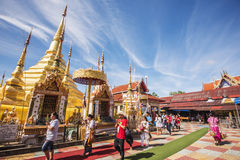 Buddhist people praying and walking around a golden pagoda. Stock Photos
