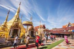 Buddhist people praying and walking around a golden pagoda. Stock Photos