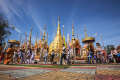 Buddhist people praying and walking around a golden pagoda. Stock Image