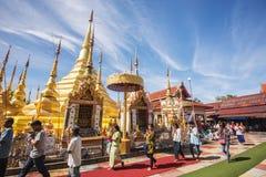 Buddhist people praying and walking around a golden pagoda. Stock Photo
