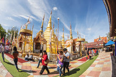 Buddhist people praying and walking around a golden pagoda. Stock Images