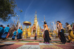 Buddhist people praying and walking around a golden pagoda. Royalty Free Stock Images