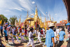 Buddhist people praying and walking around a golden pagoda. Royalty Free Stock Photos