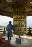 Buddhist pilgrim praying with a prayer wheel in Chimi Lhakang Monastery, Bhutan Royalty Free Stock Photography