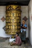 Buddhist pilgrim praying with a prayer wheel in Chimi Lhakang Monastery Stock Image