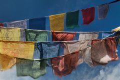 Buddhist prayer flags, colors red, blue, green, yellow and white with mantra texts, fluttering in the wind against blue sky backgr Stock Image