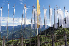 Buddhist Prayer Flags with mountains background - Bhutan. Buddhist Prayer Flags on a road bridge in the mountains near Trashigang - Eastern Bhutan Stock Photo