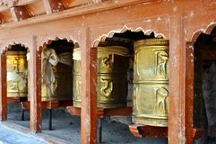 Buddhist prayer wheels. Ladakh, Little Tibet (India) - Golden Buddhist prayer wheels in a row Stock Photography