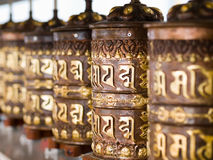 Buddhist Prayer Wheels. A row of prayer wheels with mantras inscribed in Sanskrit Stock Photos