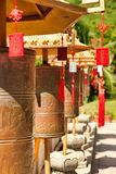 Buddhist prayer wheels in front of the temple jade-gold statue of the goddes Guanyin in the Nanshan park. On prayer wheels Mantra stock images