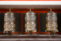 Buddhist prayer wheels in Tibetan monastery with written mantra. Himalayan village, Nepal Stock Photo