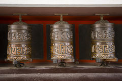 Buddhist prayer wheels in Tibetan monastery with written mantra. Himalayan village, Nepal Royalty Free Stock Photos