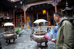 Buddhist prayers burning incense. In a temple in Sichuan, China stock images