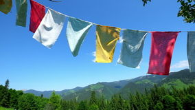 Buddhist praying flags fluttering in the wind over blue sky stock footage