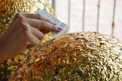 Buddhist puts gold leaf on round stone Royalty Free Stock Photo