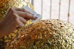 Buddhist puts gold leaf on round stone Royalty Free Stock Photo