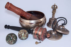 Buddhist religious objects for the performance of rituals. Singing bowl, prayer wheel, magic balls and bell on a white background stock photos