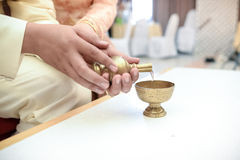 Buddhist's grail pouring water Stock Images
