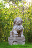 Buddhist sculpture. Chinese guardian lion statue in bush. Royalty Free Stock Image