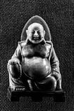 Buddhist statue. Black and white Buddhist statue with a textured background stock image