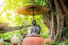 Buddhist statue meditating under big tree. Buddhist statue meditating under big tree atThaiand Royalty Free Stock Photo