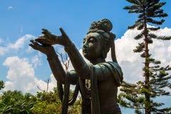Buddhist Statue Praising Tian Tan Buddha. Buddhist statue praising and making offerings to the Tian Tan Buddha. The Po Lin Monastery and the Lantau Peak in the Stock Photo