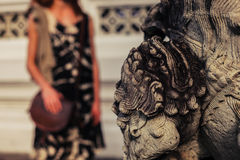 Buddhist statue with woman in background Royalty Free Stock Photo
