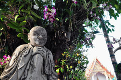 Buddhist statues and orchids Royalty Free Stock Photo