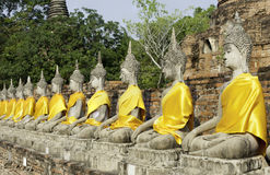 Buddhist statues in a row. A row of Buddhist statues decorated on golden cloth Ayuthaya Thailand Stock Photo