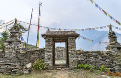 Buddhist stone made gate with prayer flags Stock Images