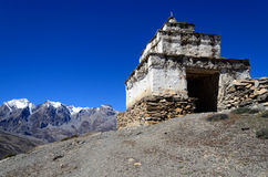 Buddhist stone stupa with mountain in background. White buddhist stone stupa with mountain in background, Chharka Village, Dolpo Region, Nepal Royalty Free Stock Image