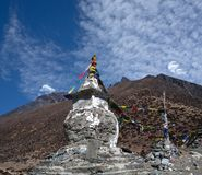 Buddhist stupa above Dingboche on the way to Everest base camp,. Ancient Buddhist stupa with prayer flags above Dingboche village on the way to Everest base camp stock image