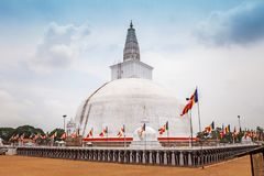 Buddhist stupa in Anuradhapura, Sri Lanka. Stupa called Ruwanweliseya wrapped with orange cloth and elephant statues Royalty Free Stock Images