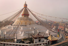 Buddhist Stupa Bodnath: the second largest Buddhist stupa immense white, with a gold head of Buddha, evening, people go and pray, Stock Image