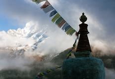 Buddhist Stupa with prayer flags and Thamserku peak - Nepal Stock Photo