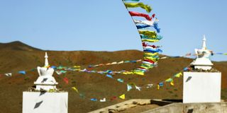 Buddhist stupa and prying flag in the desert gobi, Mongolia royalty free stock image