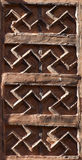 Buddhist Swastika Architecture. Buddhist swastikas carved into the side of a building at a Buddhist village Stock Photo