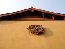 Buddhist symbol on temple. Low angle view of wooden Buddhist prayer wheel on exterior wall of Chinese temple Stock Photos